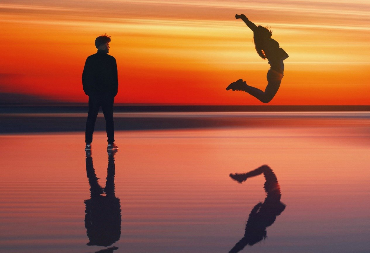 two people on beach with sunset behind them. One person jumping in air